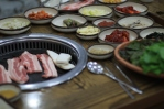Samgyeopsal is a Korean dish which consists of unseasoned/unmarinated pork belly meat cooked and eat directly from a grill. It is usually served with two sauces: ssamjang (K쌈장) and gireumjang (기름장) sauces, and various Banchan (반찬) accompaniments.